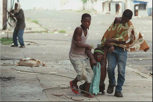 Liberian rebels loyal to Charles Taylor's National Patriotic Front of Liberia (NPFL) run from the front-line carrying a wounded comrade as rival ULIMO soldiers loyal to Roosevelt Johnson pushed them back from the Barclay Training Center in downtown Monrovia Monday, May 6, 1996. Fighting continued in the Liberian capital into the afternoon past a noon cease-fire called by warlords, prompting US Marines to fire at rebels battling in the streets near the US embassy. (Photo by David Guttenfelder/AP Photo)