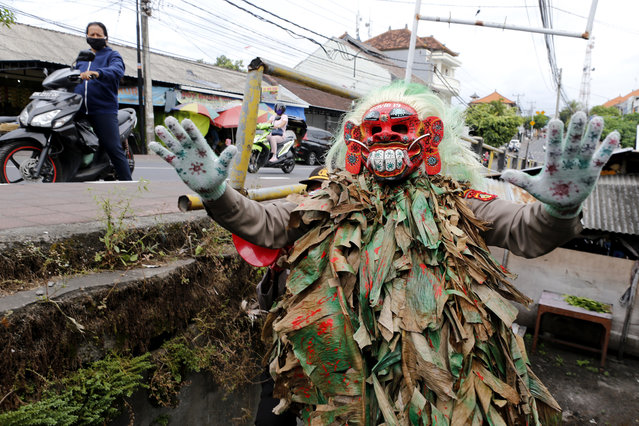 A police officer wearing a Balinese traditional mask, called celuluk, performs as the new coronavirus during a campaign to wear masks as a precaution against the virus outbreak at a market in Bali, Indonesia, Thursday, May 14, 2020. (Photo by Firdia Lisnawati/AP Photo)