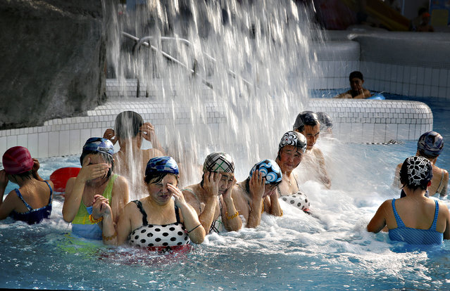 North Koreans cover their face from the splash of a water feature in the indoor section of the Munsu water park on Tuesday, December 1, 2015, in Pyongyang, North Korea. The water park is opened to both tourists as well as locals living in the North Korean capital. (Photo by Wong Maye-E/AP Photo)