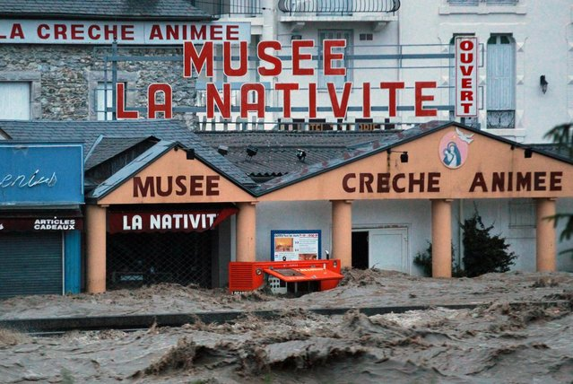 Shops in the center of Lourdes , southwestern France, under water Tuesday, June 18, 2013. French rescue services and police are evacuating hundreds of pilgrims from hotels threatened by floodwaters from a rain-swollen river in the Roman Catholic shrine town of Lourdes. (Photo by Bob Edme/AP Photo)