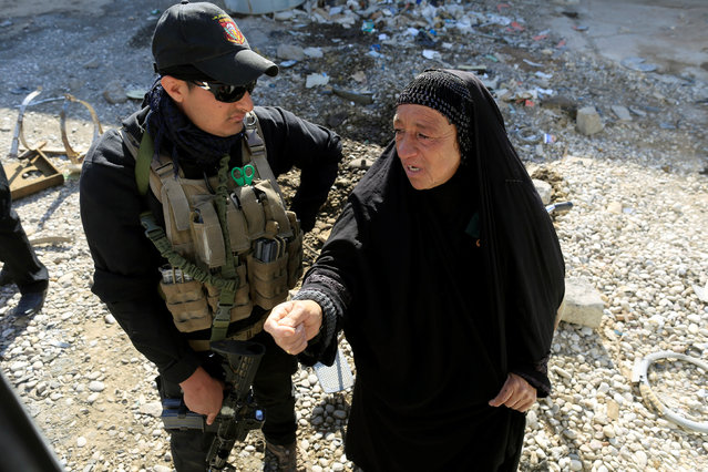 A special forces fighter listens to a woman who just fled Samah district of eastern Mosul before she boards a bus at their checkpoint in Kokjali, east of Mosul, Iraq November 5, 2016. (Photo by Zohra Bensemra/Reuters)