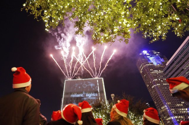 People enjoy fireworks and the dazzling display of more than 550,000 LED lights during the Reliant Lights Your Holidays at the AT&T Performing Arts Center on Saturday, December 5, 2015, in Dallas, TX. (Photo by Brandon Wade/Invision for Reliant/AP Images)