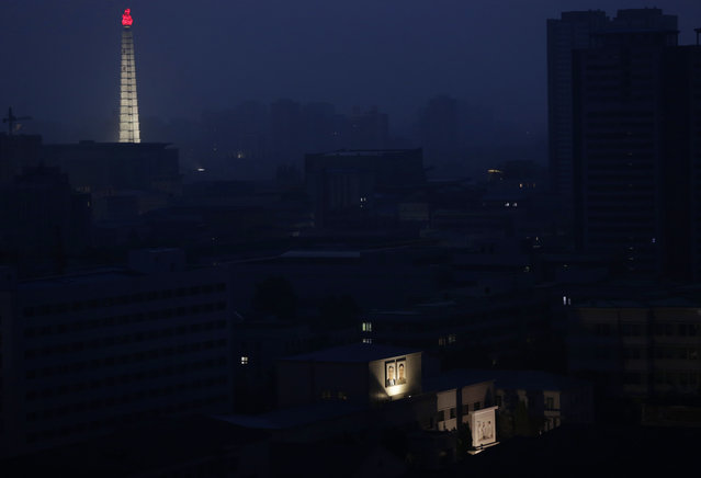 Portraits of the late North Korean leaders Kim Il Sung and Kim Jong Il are illuminated on a building as the Tower of Juche Idea is seen in the background at dawn in Pyongyang, North Korea, Tuesday, June 19, 2018. (Photo by Dita Alangkara/AP Photo)