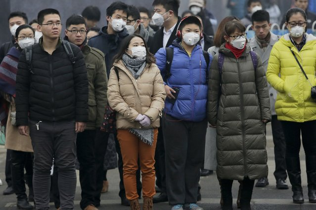 "Morning commuters wear protective masks to shield from extreme smog in central Beijing December 8, 2015 as China's capital issues its first ever ""red alert"" for pollution. (Photo by Damir Sagolj/Reuters)"
