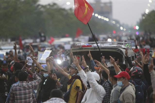 Protesters flash the three-fingered salute as they march in Mandalay, Myanmar, on Monday, February 8, 2021. Tension in the confrontations between the authorities and demonstrators against last week's coup in Myanmar boiled over Monday, as police fired a water cannon at peaceful protesters in the capital Naypyitaw. (Photo by AP Photo/Stringer)