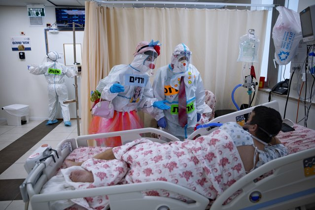 Clowns wearing protective equipment entertain a COVID-19 patient in the intensive care ward for coronavirus patients at Shaare Zedek Medical Center in Jerusalem, Monday, November 23, 2020. (Photo by Oded Balilty/AP Photo)