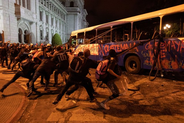 Protesters try to topple a damaged bus outside the National Palace demanding the resignation of President Alejandro Giammattei, in Guatemala City, Saturday, November 28, 2020. Protests continue against Giammattei and the legislature for approving a budget that cut educational and health spending. Guatemala's Congress backed down on Monday on the proposed federal budget. (Photo by Moises Castillo/AP Photo)