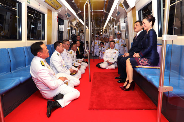 This photo taken on November 14, 2020 shows Thailand's King Maha Vajiralongkorn and Queen Suthida riding with officials on an MRT commuter train during the inauguration of a new subway station in Bangkok. (Photo by Royal Household Bureau/Reuters)