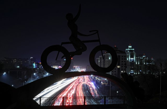 Traffic flows along Al-Farabi avenue, as a sculpture of a bicyclist is seen in the foreground, in Almaty, Kazakhstan December 29, 2020. Picture taken with long exposure. (Photo by Pavel Mikheyev/Reuters)