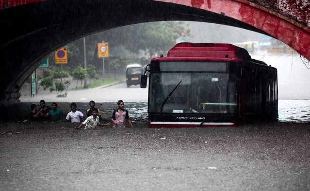 Indians wade past a bus submerged in rainwater in New Delhi, India, Saturday, July 20, 2013. Heavy rainfall lashed the national capital Saturday, flooding streets and homes and choking the city with traffic jams. (Photo by AP Photo)