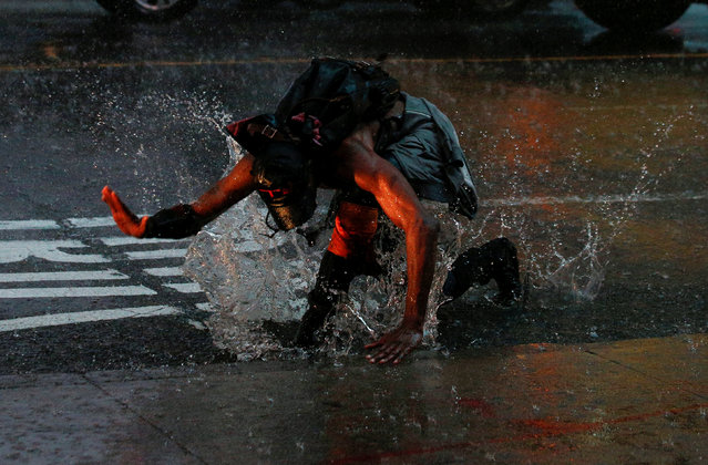 A man splashes in a puddle in Times Square during a heavy midday downpour in New York City, U.S., July 17, 2018. (Photo by Brendan McDermid/Reuters)