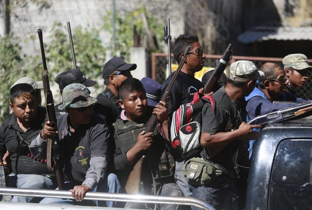 Members of the Community Police of the FUSDEG (United Front for the Security and Development of the State of Guerrero) travel at the back of a lorry towards a hill, where their colleagues had a shootout with a group that villagers suspected of belonging to a local gang, in the village of Petaquillas, on the outskirts of Chilpancingo, in the Mexican state of Guerrero, February 1, 2015. (Photo by Jorge Dan Lopez/Reuters)