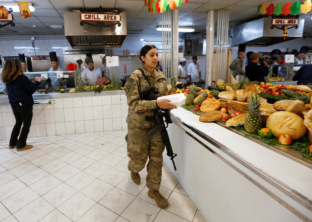 A U.S. soldier carries a container of food during a Thanksgiving meal at a NATO base in Kabul, Afghanistan November 24, 2016. (Photo by Mohammad Ismail/Reuters)
