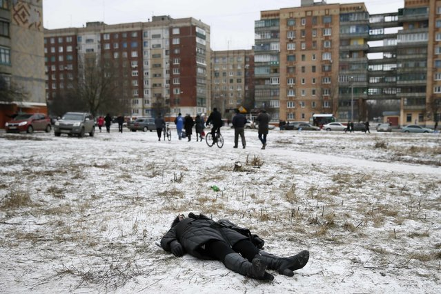 The body of a woman killed by recent shelling lies on a street in the residential sector in the town of Kramatorsk, eastern Ukraine February 10, 2015. (Photo by Gleb Garanich/Reuters)