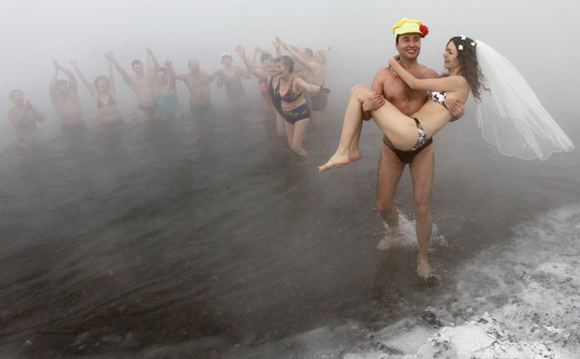 Sergey Kaunov, a member of a local winter swimmers' club, carries his bride Irina Kuzmenko out of water as they celebrate their wedding on the bank of Yenisey River where the air temperature was about -30 degrees Celsius (-22 degree Fahrenheit) in the Russia's Siberian city of Krasnoyarsk, January 22, 2011. Irina does not practice winter bathing, but she did it on the day of their wedding after heating up in a sauna. (Photo by Ilya Naymushin/Reuters)