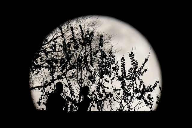 A couple are silhouetted against the rising full moon as they gather in a park, Sunday, March 28, 2021, in Kansas City, Mo. (Photo by Charlie Riedel/AP Photo)