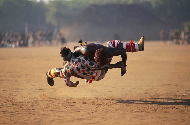Waura Indians wrestle during this year's 'quarup,' a ritual held over several days to honour in death a person of great importance to them, in Xingu National Park, Mato Grosso State, August 25, 2013. This year the Waura tribe honoured their late cacique (chief) Atamai, who died in 2012, for his work creating the Xingu Park and his important contribution in facilitating communication between white Brazilians and Indians. Picture taken August 25, 2013. (Photo by Ueslei Marcelino/Reuters)