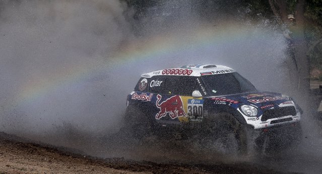 A rainbow forms as Mini pilot Nasser Al-Attiyah of Qatar drives his car through the water during the Buenos Aires-Rosario prologue stage of Dakar Rally 2016 in Arrecifes, Argentina, January 2, 2016. (Photo by Marcos Brindicci/Reuters)