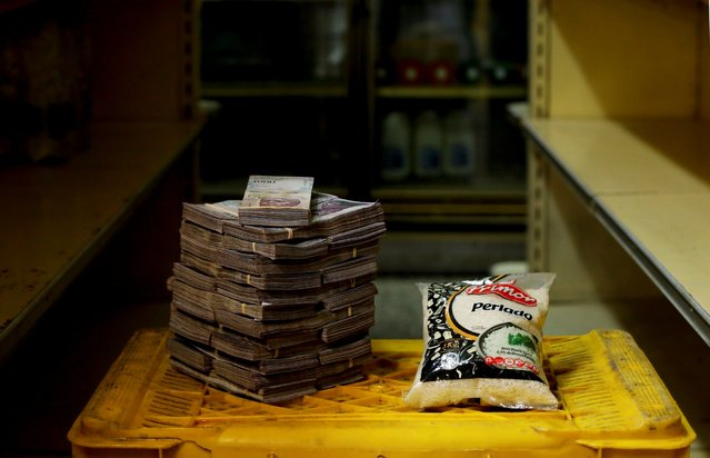 A package of 1kg of rice is pictured next to 2,500,000 bolivars, its price and the equivalent of 0.38 USD, at a mini-market in Caracas, Venezuela August 16, 2018. It was the going price at an informal market in the low-income neighborhood of Catia. (Photo by Carlos Garcia Rawlins/Reuters)