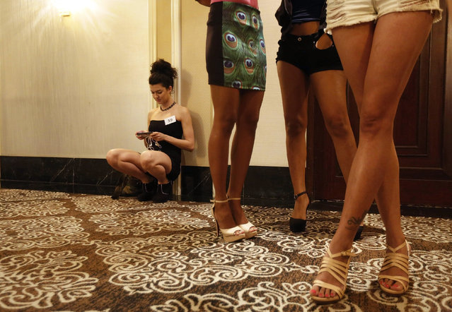 An aspiring model looks at her phone as she waits with others for their turn to be judged during auditions for the upcoming Lakme Fashion Week in Mumbai February 12, 2015. (Photo by Shailesh Andrade/Reuters)