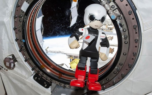 Humanoid communication robot Kirobo holding Japanese national flag and speaking during session to check success of its first conveyance into space, at International Space Station. (Photo by NASA/Reuters/2013.Kibo-Robot)