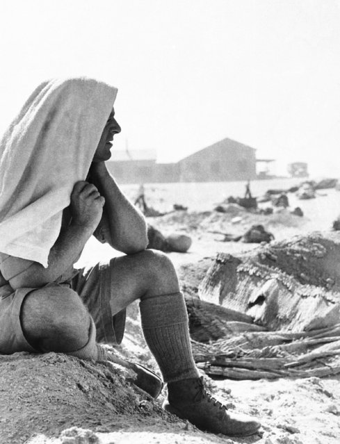 An Australian soldier in Egypt, with a towel over his head to keep off the scorching sun and driven, surveys his camp, December 13, 1940 in Egypt. Although the climate is hot in the daytime, soldiers sleep under blankets for protection against the cold night. Australian troops have joined other British forces in the campaign against the Italian army in Egypt. (Photo by AP Photo)