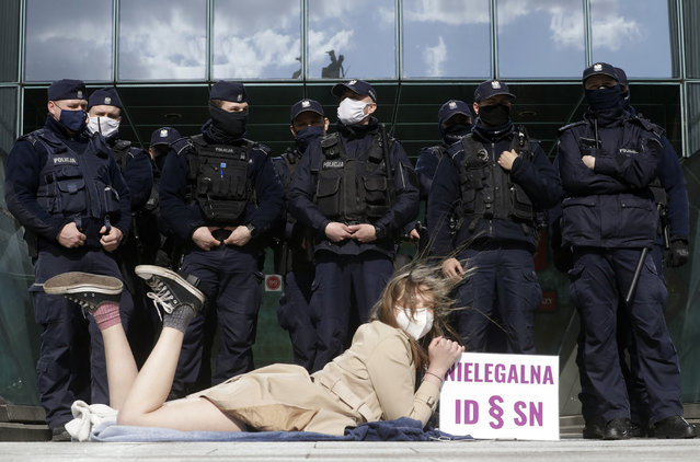 """Policemen guard Poland's Supreme Court as a protester lies on the pavement in Warsaw, Poland, on Thursday, April 22, 2021. A disputed disciplinary body within Poland's Supreme Court is examining a motion that could result in the arrest of a judge who has become a symbol of the fight for an independent judiciary. The Disciplinary Chamber is due to decide whether to force Judge Igor Tuleya to answer to prosecutors about charges related to a ruling that went against the interests of the ruling Law and Justice party. Sign read in Polish """"Illegal ID – SN"""", where ID means Disciplinary Chamber and SN means Supreme Court. (Photo by Czarek Sokolowski/AP Photo)"""