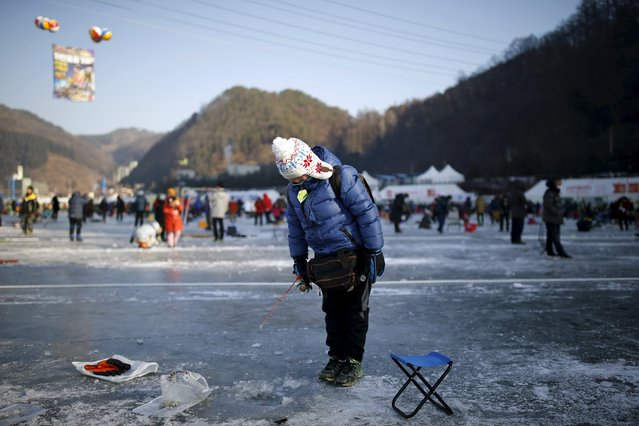 A boy fishes for trout through holes in a frozen river in Hwacheon, south of the demilitarized zone (DMZ) separating the two Koreas, January 9, 2016. (Photo by Kim Hong-Ji/Reuters)