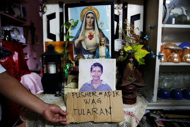 """A relative holds a cardboard sign next to a picture of Florjohn Cruz inside the house where he was killed in a police drugs buy-bust operation in Manila, Philippines late October 20, 2016. The sign, which the family said they found at the house, translates as """"PUSHER AND ADDICT – DON'T IMITATE"""". (Photo by Damir Sagolj/Reuters)"""