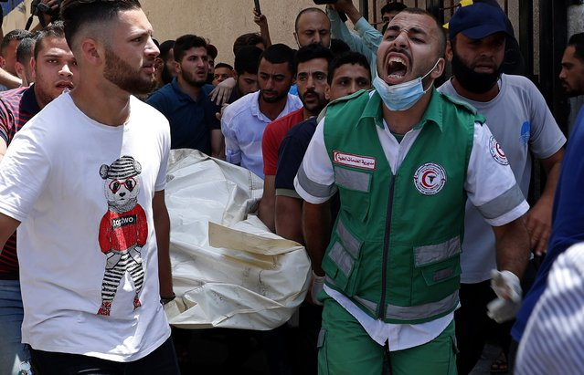 Medics and youths chant while carrying the covered body of a man, who was killed in Israeli airstrikes that hit his apartment building, in Gaza City, Tuesday, May 11, 2021. Since Monday, Gaza militants have fired hundreds of rockets toward Israel. Israel has fired back, hitting targets inside Gaza that included a high-rise building in the middle of Gaza City. (Photo by Adel Hana/AP Photo)