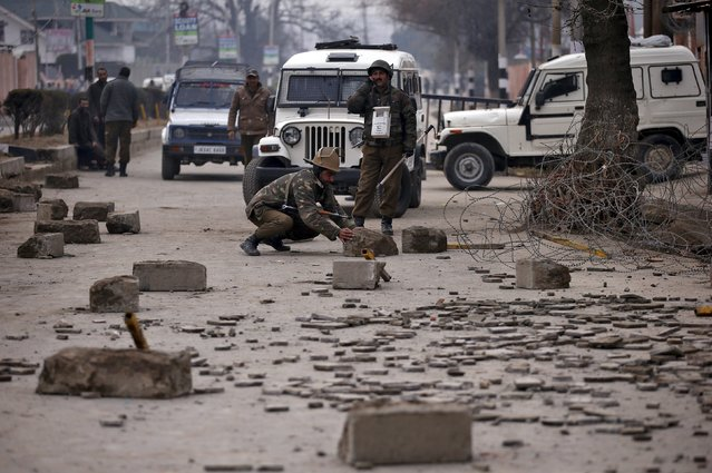 An Indian policeman prepares to clear a road during a protest in Srinagar, January 14, 2016. (Photo by Danish Ismail/Reuters)
