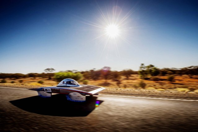 The Indupol One of the Belgian solar team rides across a desert, 285 kilometers south of Alice Springs, Australia, on Oktober 8, 2013. The solar challenge race, lasting for seven days, will take 43 participants over 3,021 kilometers before ending on Sunday. (Photo by Geert Vanden Wijngaert/Associated Press)