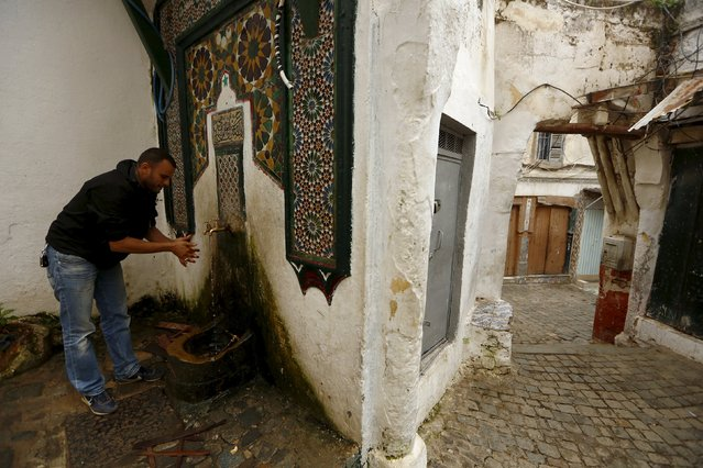 A man performs ablution using water at an old fountain before performing prayers in the old city of Algiers Al Casbah, Algeria December 3, 2015. (Photo by Zohra Bensemra/Reuters)