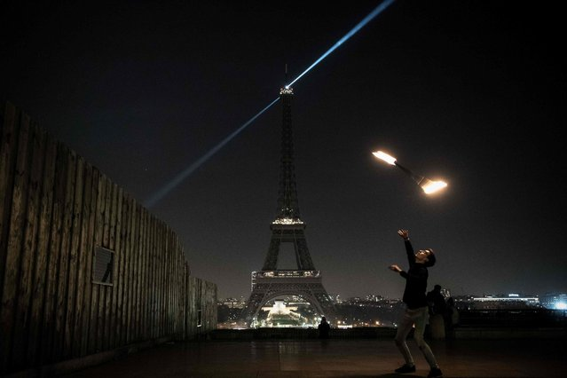 A man juggles with a stick on fire in front of the Eiffel tower with lights off, in Paris, December 14, 2016, in support of the Syrian city of Aleppo. (Photo by Philippe Lopez/AFP Photo)