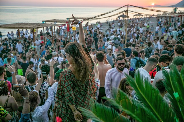 People dance during the Unum Festival at Rana e Hedhun beach on June 5, 2021 in Shengjin, Albania. International electronic musicians like Ben Klock and Sven Vath are attending the Unum Festival in Albania. (Photo by Ferdi Limani/Getty Images)
