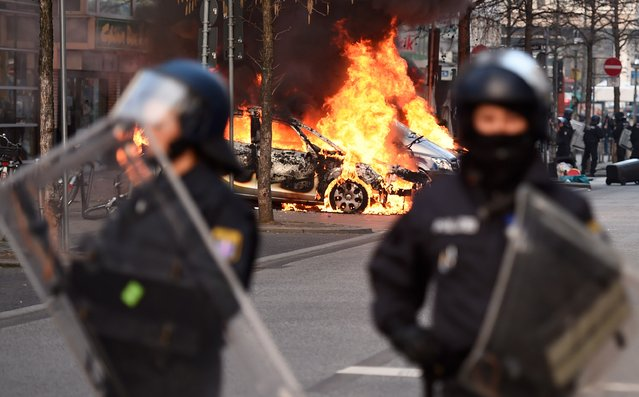 Riot Police form a cordon as a Police car burns on the opening day of the European Central Bank (ECB) in Frankfurt am Main, western Germany, on March 18, 2015. Supporters of the so-called Blockupy alliance consisting of social movements, activists, workers, trade unions and parties are expected to stage large protests against austerity and the authority of the European Central Bank when the bank's new headquarters officially will be on March 18, 2015. (Photo by Odd Andersen/AFP Photo)