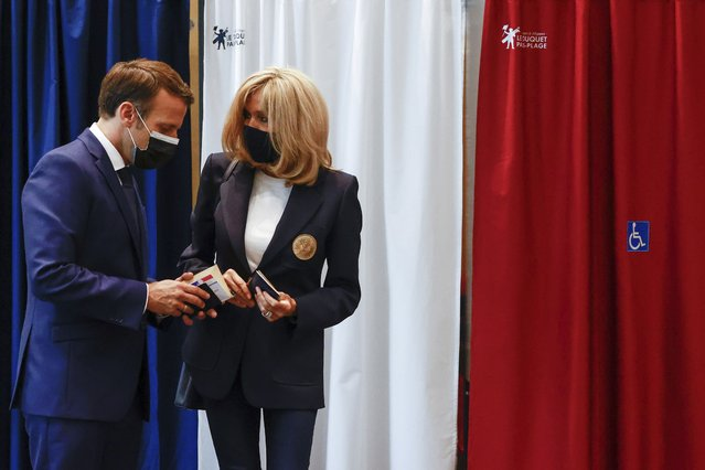 French President Emmanuel Macron chats with his wife Brigitte during the first round of French regional and departmental elections, in Le Touquet-Paris-Plage, northern France, Sunday, June 20, 2021. The elections for leadership councils of France's 13 regions, from Brittany to Burgundy to the French Riviera, are primarily about local issues like transportation, schools and infrastructure. But leading politicians are using them as a platform to test ideas and win followers ahead of the April presidential election. (Photo by Christian Hartmann/Pool via AP Photo)