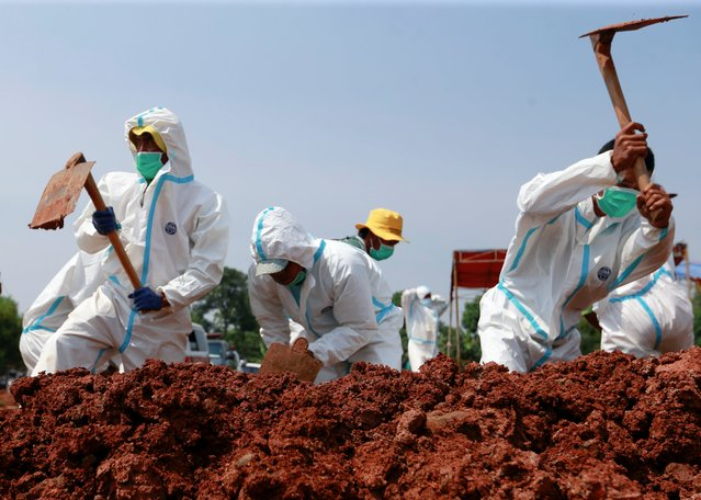 Gravediggers wearing personal protective equipment (PPE) bury a coffin at a Muslim burial area provided by the government for coronavirus disease (COVID-19) victims in Bekasi, on the outskirts of Jakarta, Indonesia, July 8, 2021. (Photo by Ajeng Dinar Ulfiana/Reuters)