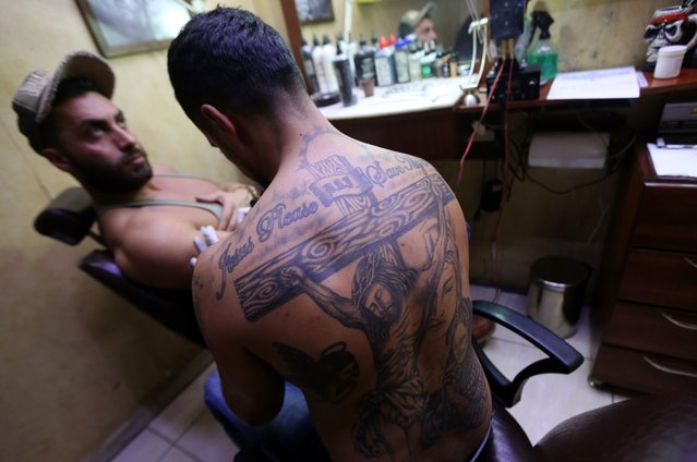 A Syrian man gets a tattoo bearing the names of his killed relatives, on February 5, 2016, in the capital Damascus. (Photo by Joseph Eid/AFP Photo)