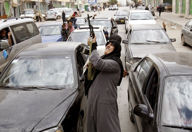 A rebel fighter supporter shoots an AK-47 rifle as she reacts to the news of the withdrawal of Libyan leader Muammar Gaddafi's forces from Benghazi March 19, 2011. The conflict was sparked by clashes in Benghazi and escalated into a rebellion that spread across the country. Gaddafi was captured and killed on October 20, 2011. Libya is currently caught up in a conflict between two rival factions who once battled together against the late Libyan leader. (Photo by Goran Tomasevic/Reuters)