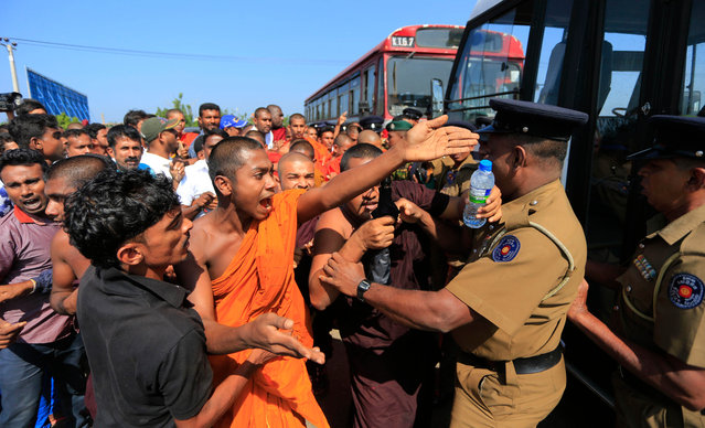 A Sri Lankan Buddhist monk and villagers argue with police officers during a protest outside the inauguration ceremony of an industrial zone in Mirijjawila village in Ambalantota, Sri Lanka, Saturday, January 7, 2017. Sri Lankan police used water cannons to try to break up violent clashes Saturday between government supporters and villagers marching against what they say is a plan to take over private land for an industrial zone in which China will have a major stake. The government has signed a framework agreement for a 99-year lease of the Hambantota port with a company in which China will have 80-percent ownership. Officials also plan to set up the nearby industrial zone where Chinese companies will be invited to set up factories. (Photo by Eranga Jayawardena/AP Photo)