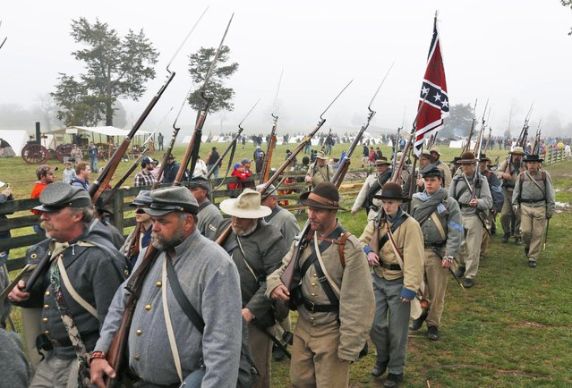 Confederate re-enactors march back to camp after a re-enactment of the Battle of Appomattox Court House as part of  the commemoration of the 150th anniversary of the surrender of the Army of Northern Virginia at Appomattox Court House in Appomattox, Va., Thursday, April 9, 2015. The battle was the final battle of the army of Confederate General Robert E. Lee before his surrender to Union troops. (Photo by Steve Helber/AP Photo)