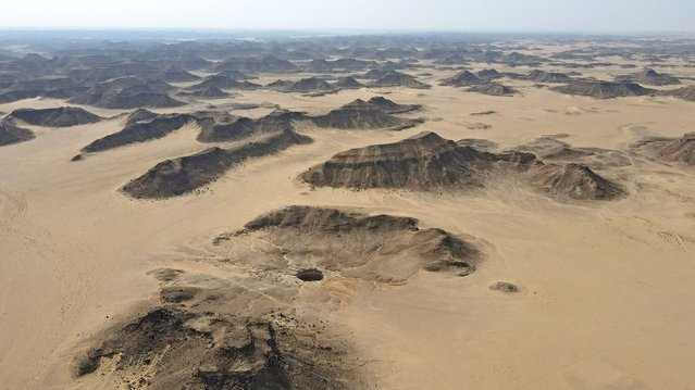 """An aerial view taken on June 6, 2021 shows the Well of Barhout known as the """"Well of Hell"""" in the desert of Yemen's Al-Mahra province. Closer to the border with Oman than to the capital Sanaa 1,300 kilometres (800 miles) away, the giant hole in the desert of Al-Mahra province is 30 metres wide and thought to be anywhere between 100 and 250 metres deep. Local folklore says it was created as a prison for the demons – a reputation bolstered by the foul odours rising from its depths. (Photo by AFP Photo/Stringer)"""