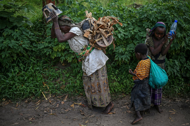 Habimana, 45, and her children walk to market to sell pottery on Idjwi island in the Democratic Republic of Congo, November 23, 2016. (Photo by Therese Di Campo/Reuters)