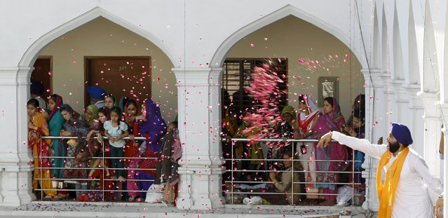 A Sikh devotee throws flower petals as the procession passes by during the Baisakhi festival at Panja Sahib shrine in Hassan Abdel April 13, 2015. (Photo by Caren Firouz/Reuters)