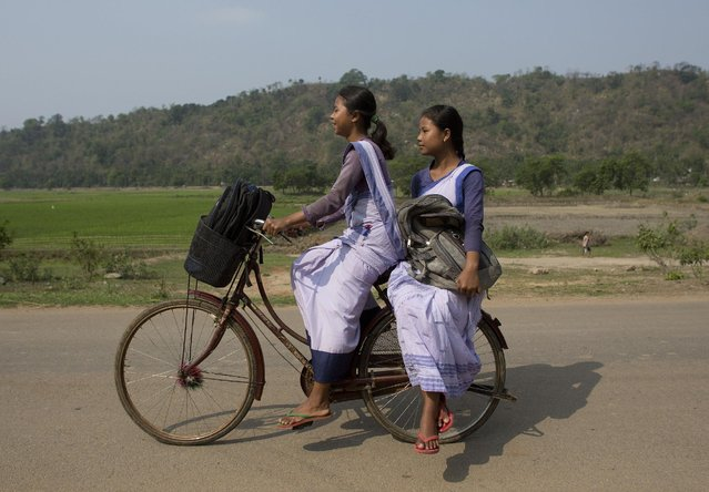 Indian girls go to a school on a bicycle at Roja Mayong village about 40 kilometers (25 miles) east of Gauhati, India, Thursday, April 9, 2015. According to the UNESCO Education for All Global Monitoring Report 2015, only half of all countries have achieved the most watched goal of universal primary enrollment. The report launched Thursday says, India has reduced its out of school children by over 90% Since 2000. (Photo by Anupam Nath/AP Photo)
