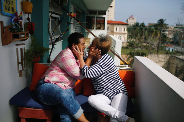 Cuban same-s*x couple Mercedes Garcia (R) and Onelia Miranda, who have been together for ten years, share a moment at the balcony of their apartment in Havana, Cuba on August 13, 2018. (Photo by Tomas Bravo/Reuters)