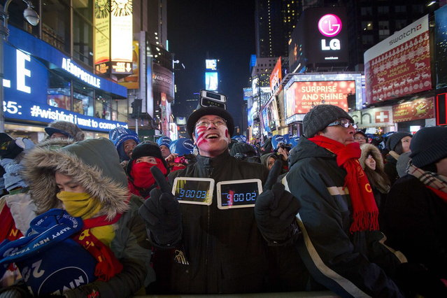 Reveller Takamas Sasaki from Tokyo looks up during New Year's Eve celebrations in Times Square in New York December 31, 2013. (Photo by Carlo Allegri/Reuters)