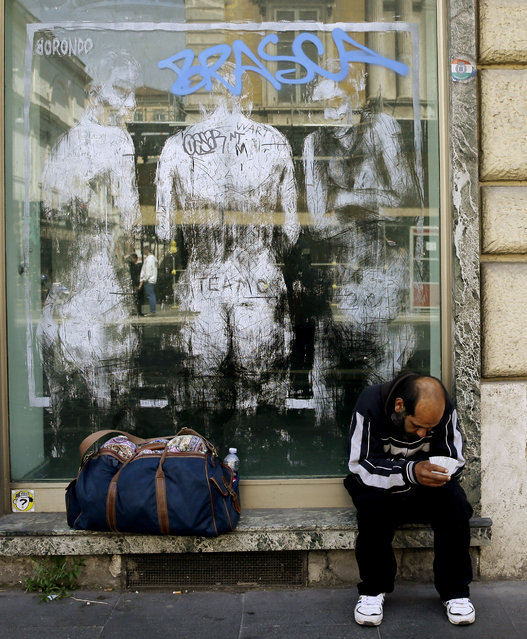 A man begs for money as he sits by a mural on a shop window in Rome, Thursday, April 16, 2015. (Photo by Gregorio Borgia/AP Photo)