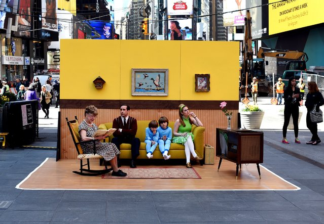 "Actors pose on a outdoor set by artist Justin Bettman during the opening of Bettman's outdoor public photography set in Times Square in New York on April 15, 2015. Made with discarded furniture and materials, the set is scheduled to remain on display through April 19, as part of Bettman's ongoing ""#SetintheStreet"" interactive installation project and coinciding with the opening of the 14th annual Tribeca Film Festival. (Photo by Timothy A. Clary/AFP Photo)"